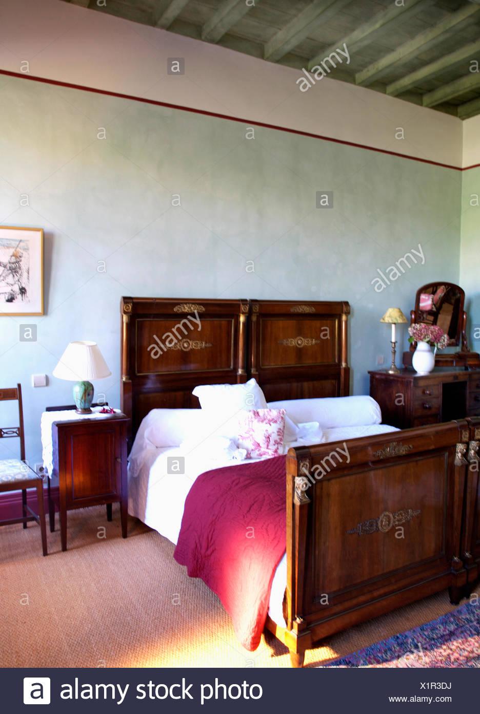 Weiße Bettwäsche und rot werfen auf antik Mahagoni Bett im ...