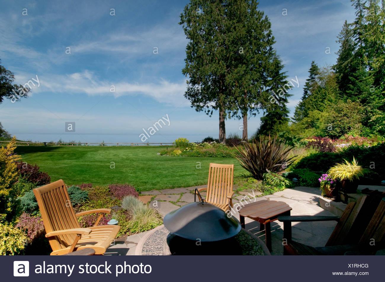 terrasse mit stÜhlen und feuerstelle im garten am meer stockfoto
