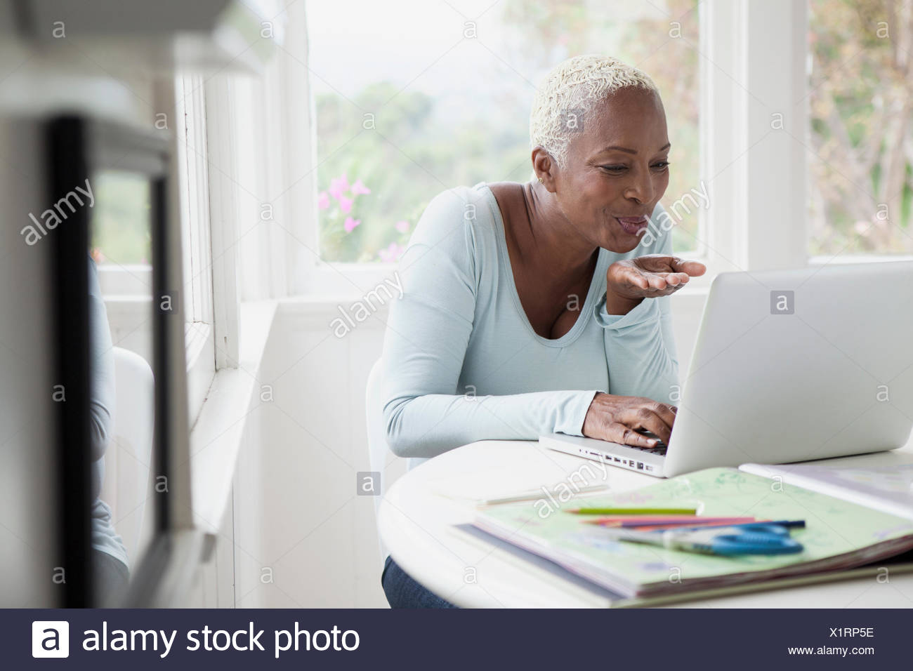 mittlere gealterte Frau bläst Küsse während Online-chat Stockbild