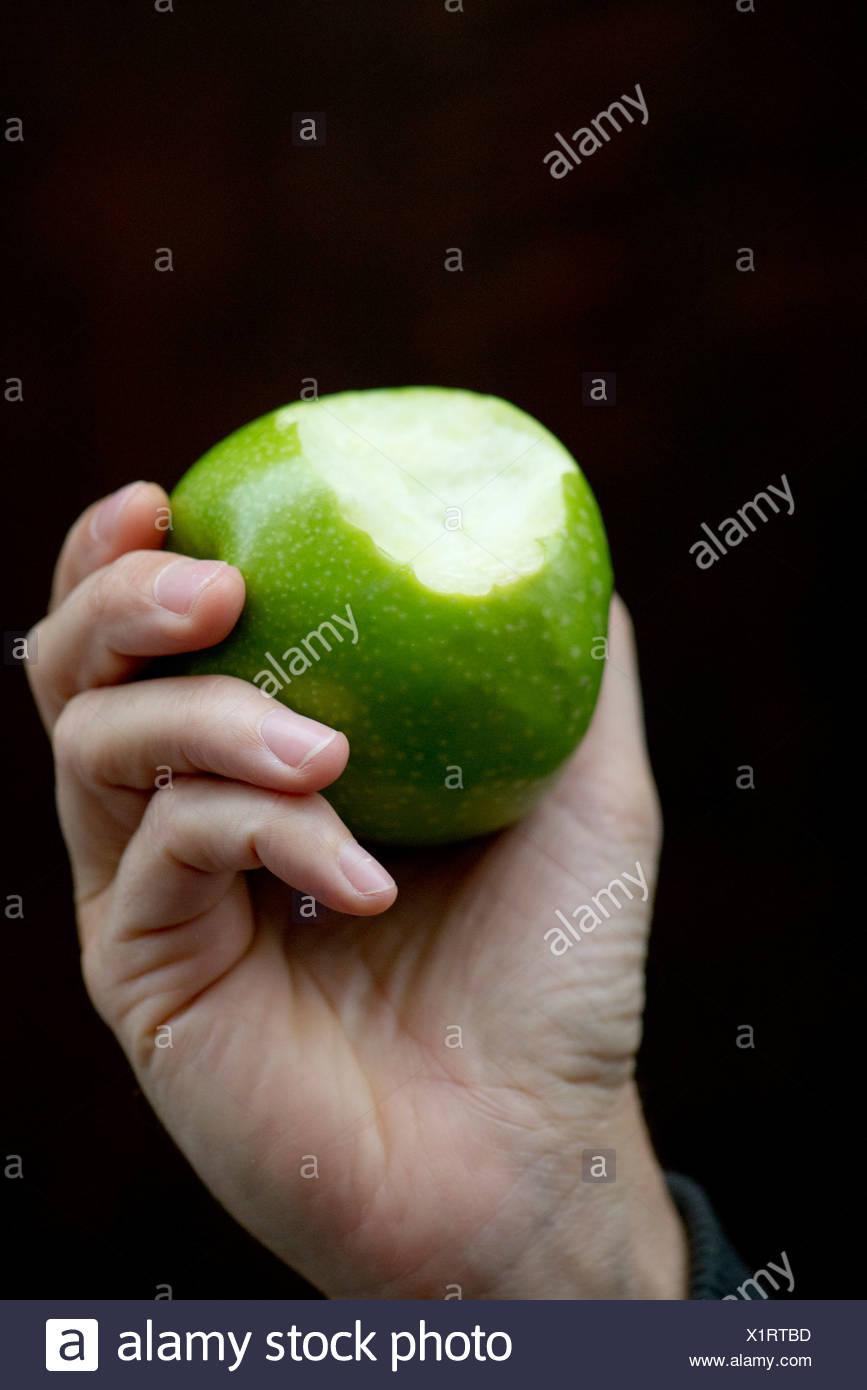 Hand hält Apfel mit Biss fehlt Stockbild