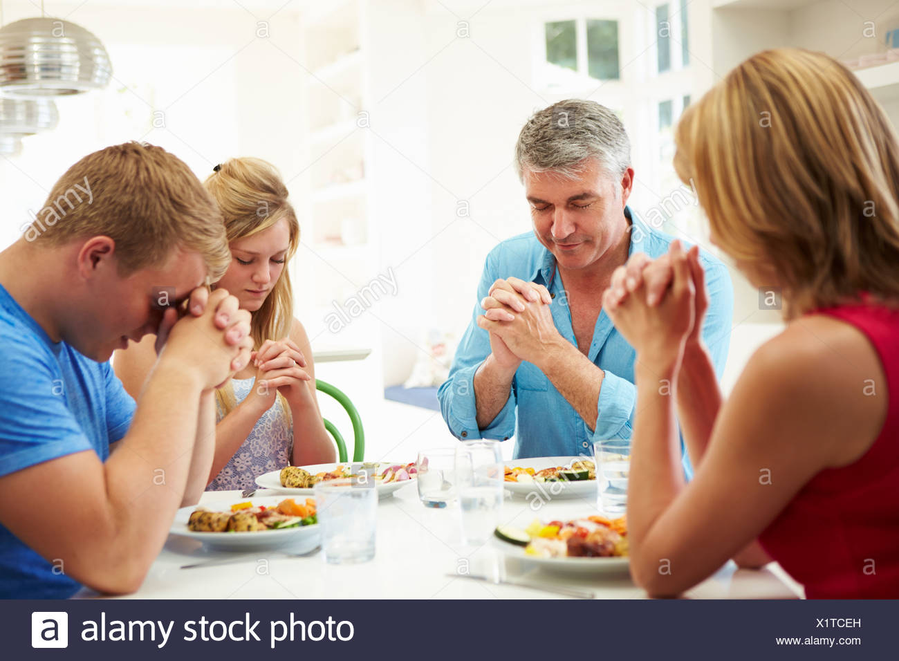 Familie Gebet vor dem Essen zu Hause zusammen Stockbild