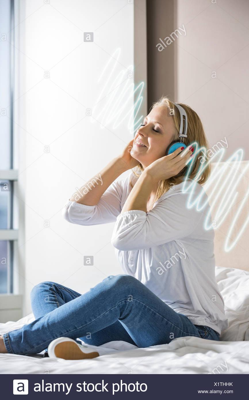 Entspannte Mitte Erwachsene Frau hören von Musik über Kopfhörer auf Bett Stockbild