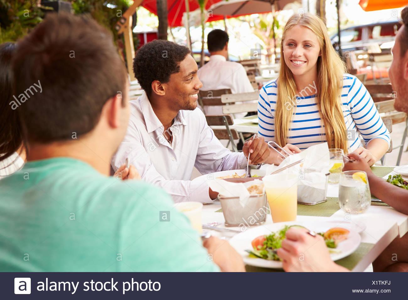 Gruppe von Freunden genießen Mittagessen im Restaurant unter freiem Himmel Stockbild