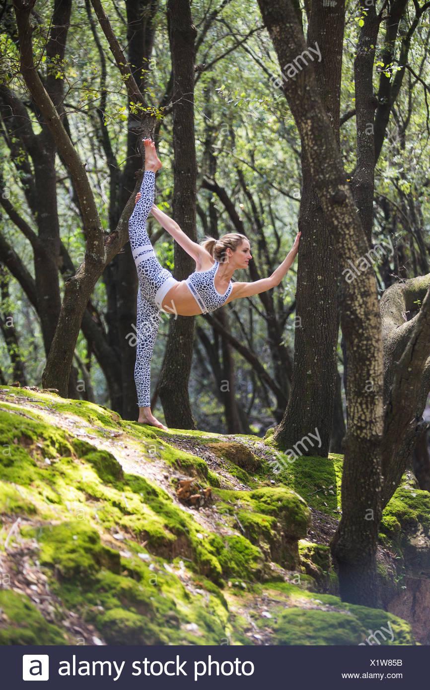 Frau auf Felsen stehend auf einem Bein Strecken Stockbild