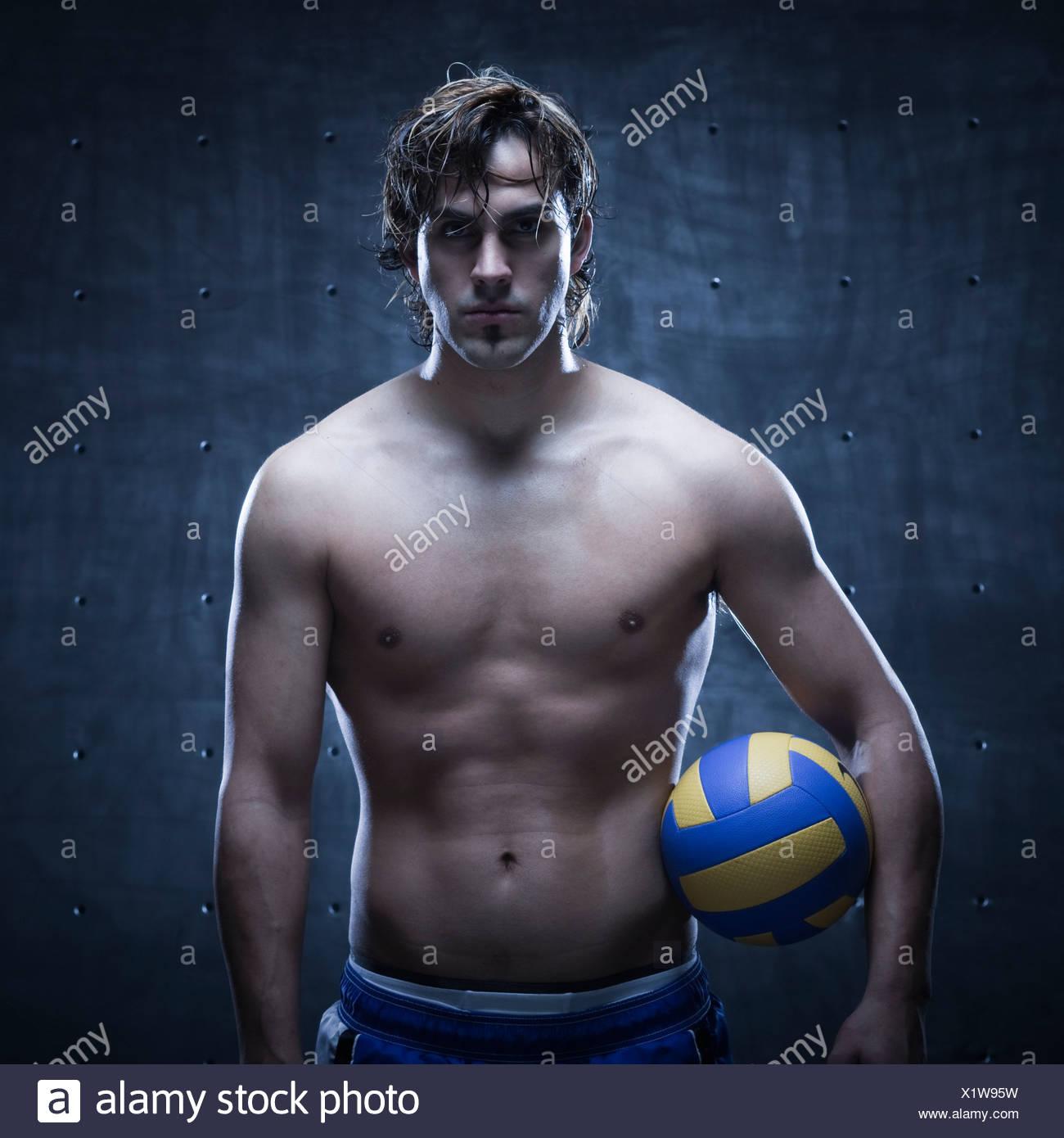 Studioaufnahme des Volleyball-Spieler stehen und Besitz ball Stockbild