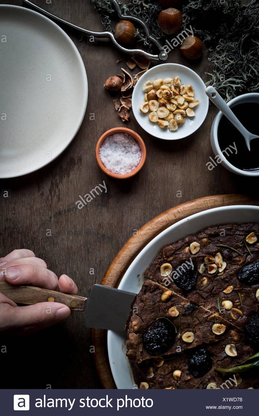 Person auf einer festlichen Mittelmeer Kastanien Mehl Kuchen in weiße Schale schneiden setzen Holztisch mit Zutaten und Weihnachten d Stockbild