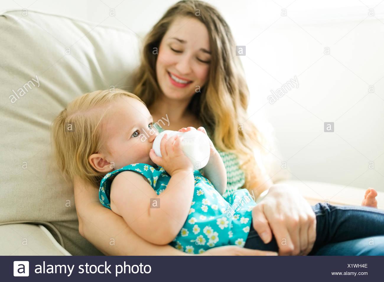 Mutter feeding baby girl (12-17 Monate) im Wohnzimmer. Stockbild