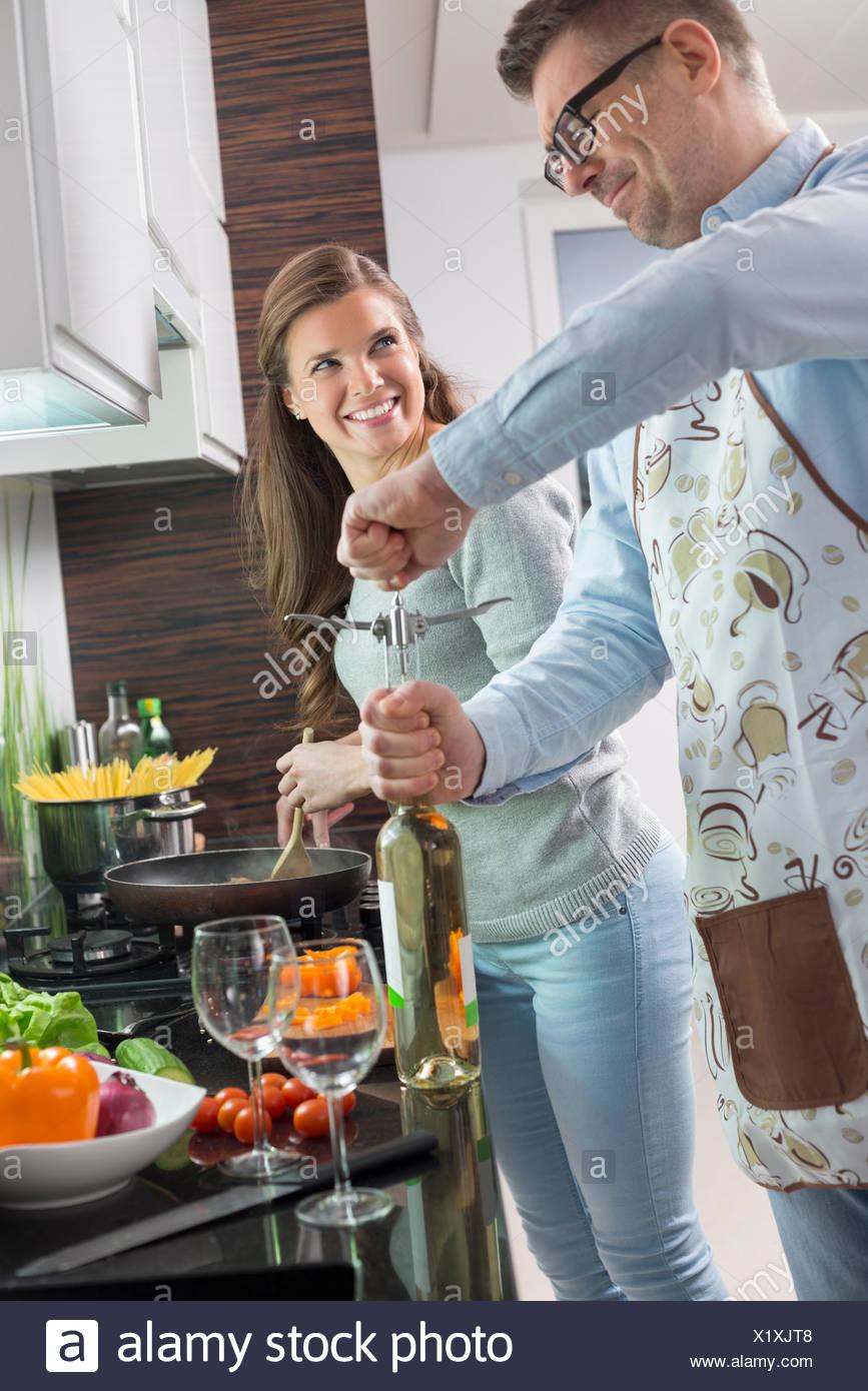 Mann, die Öffnung der Flasche Wein beim Kochen mit Frau in Küche Stockbild