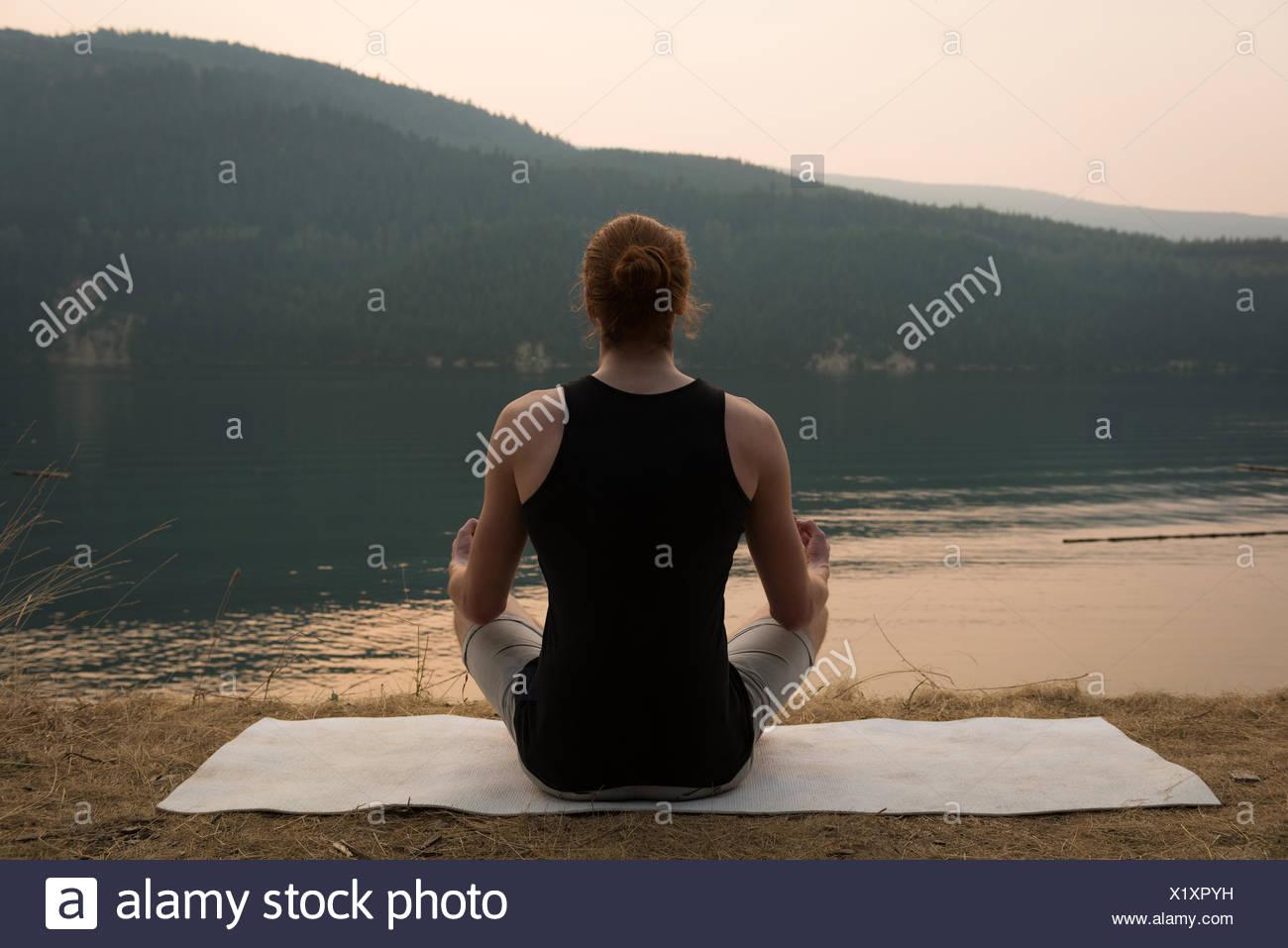 Passende Frau in Meditation Körperhaltung auf offenen Boden sitzen Stockfoto