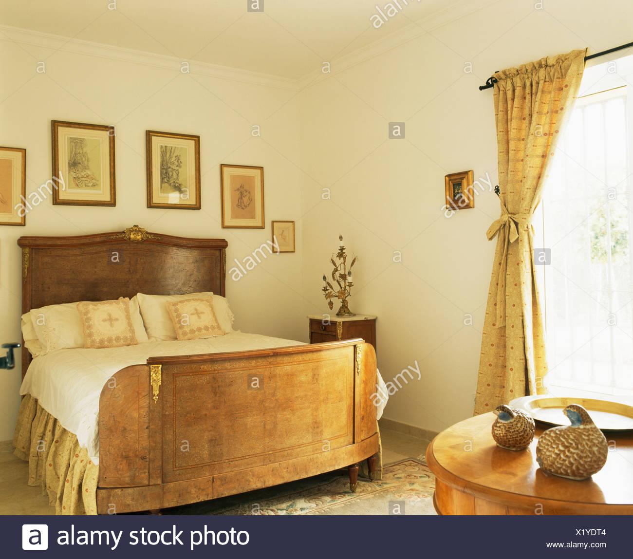 Bilder An Der Wand über Antike Mahagoni Bett In Neutral Schlafzimmer Mit  Antiken Tischchen Und Creme Vorhang Am Fenster