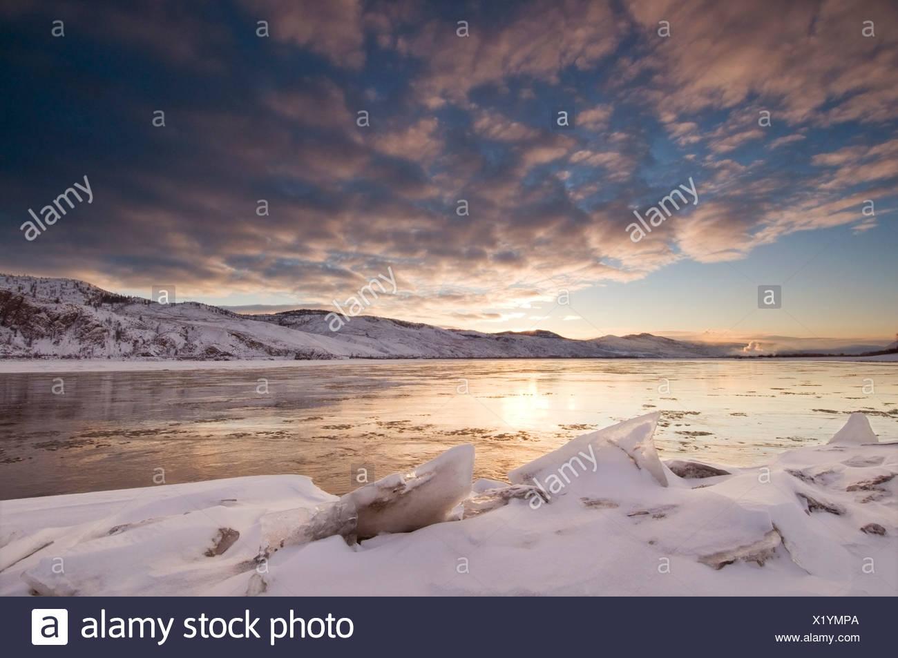 Eisbrocken erstellen Vordergrund für einen schönen Sonnenaufgang über Thompson River, wo es in Kamloops Lake gerade westlich von Kamloops fließt Stockbild