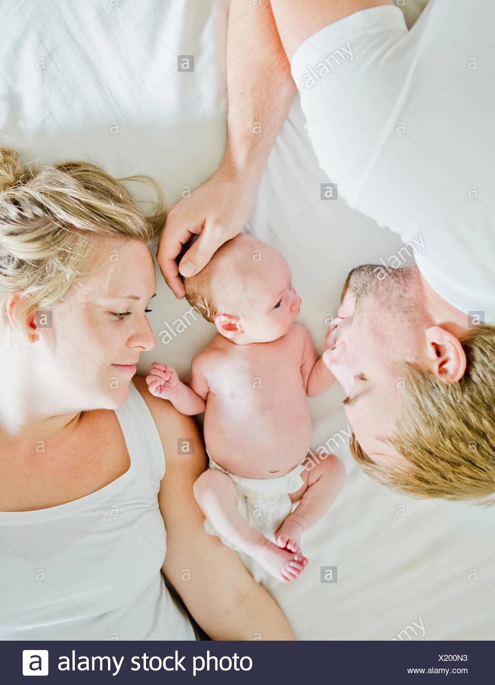 Baby Boy (0-1 Monate) mit seinen Eltern auf Bett Stockbild