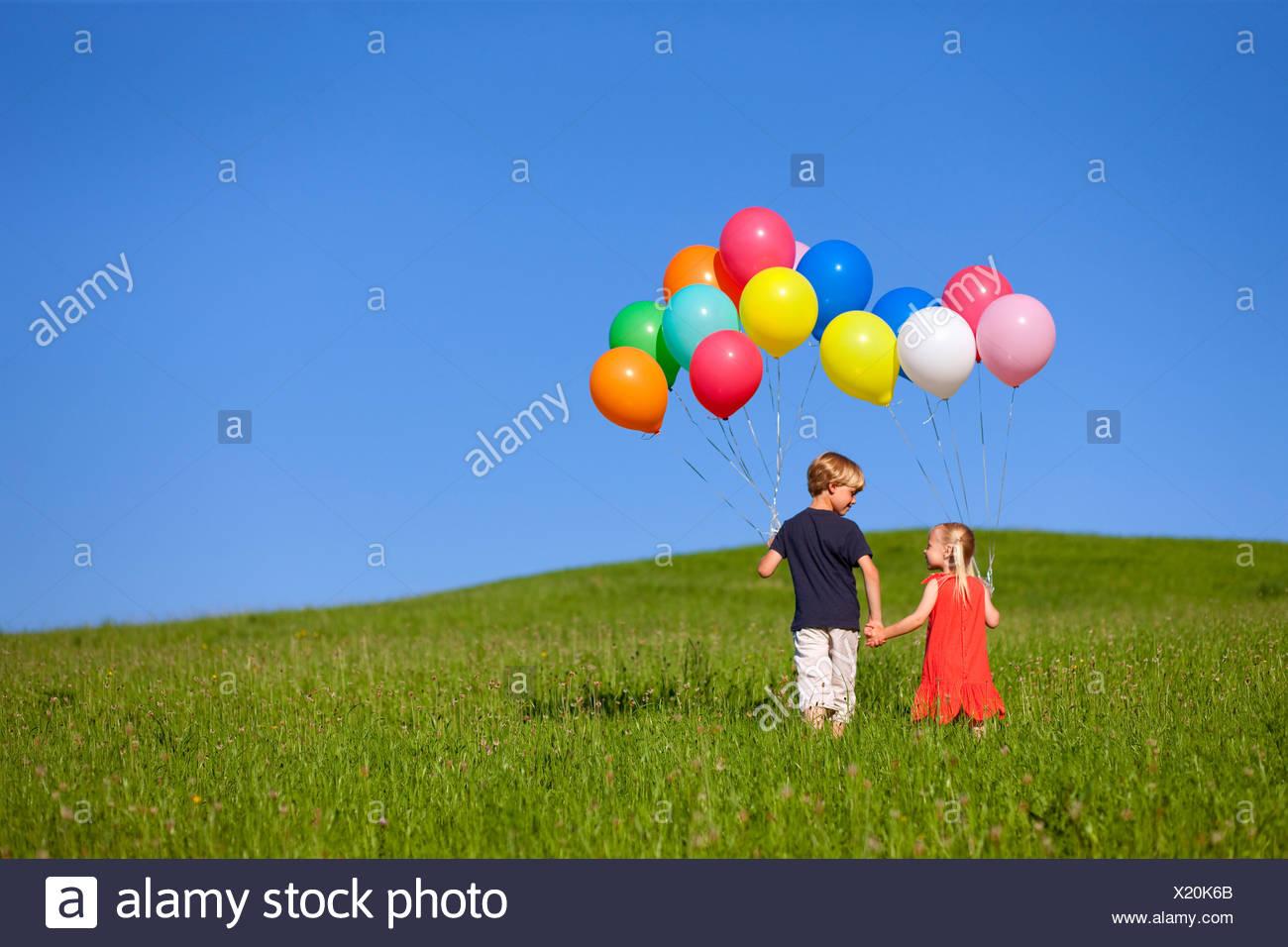 Kinder mit bunten Luftballons in Rasen Stockbild