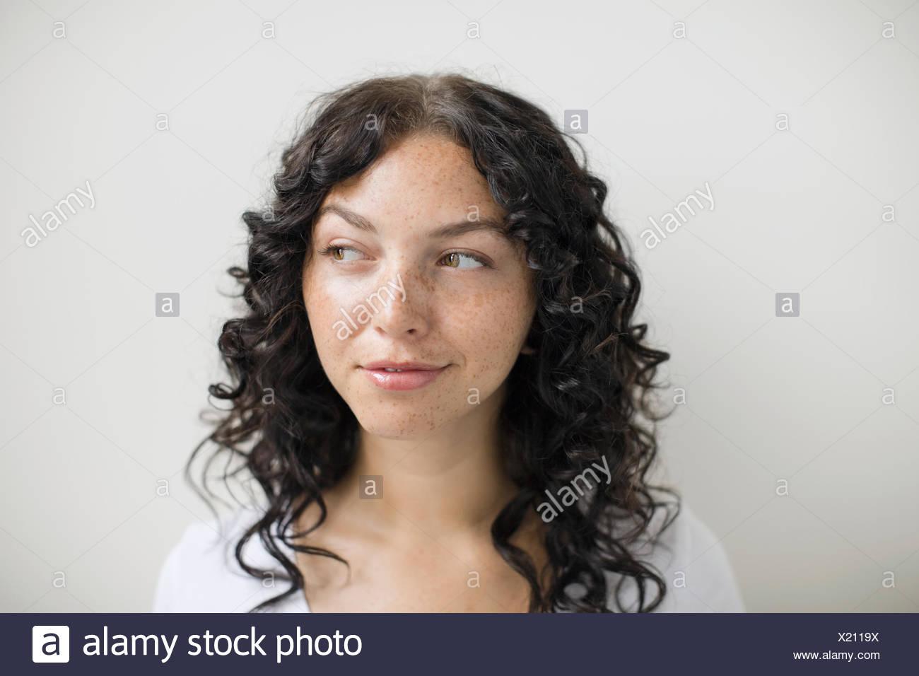 Nachdenkliche Frau mit Sommersprossen und lockiges schwarzes Haar Stockfoto