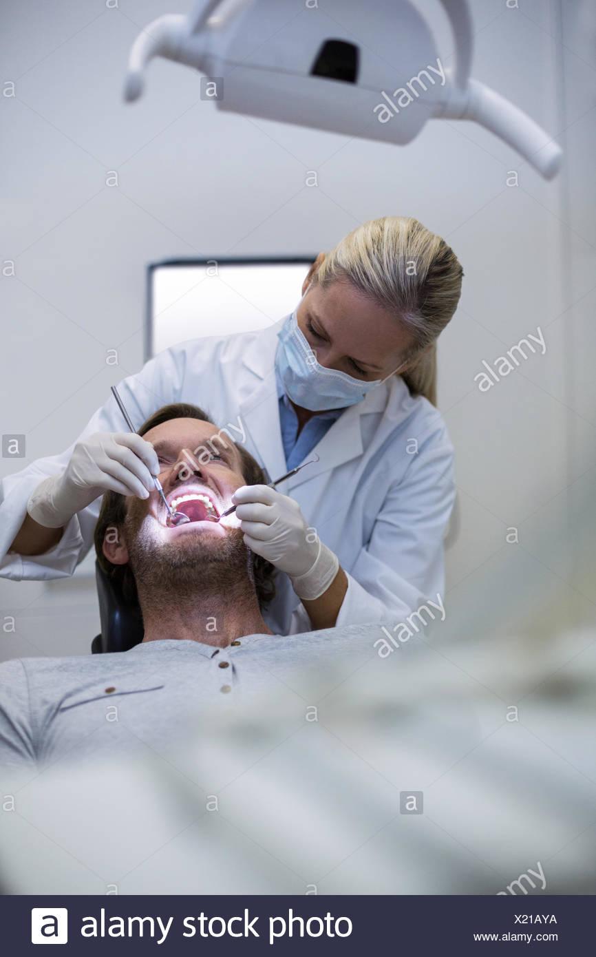 Zahnarzt, einem Patienten mit Werkzeugen Stockbild