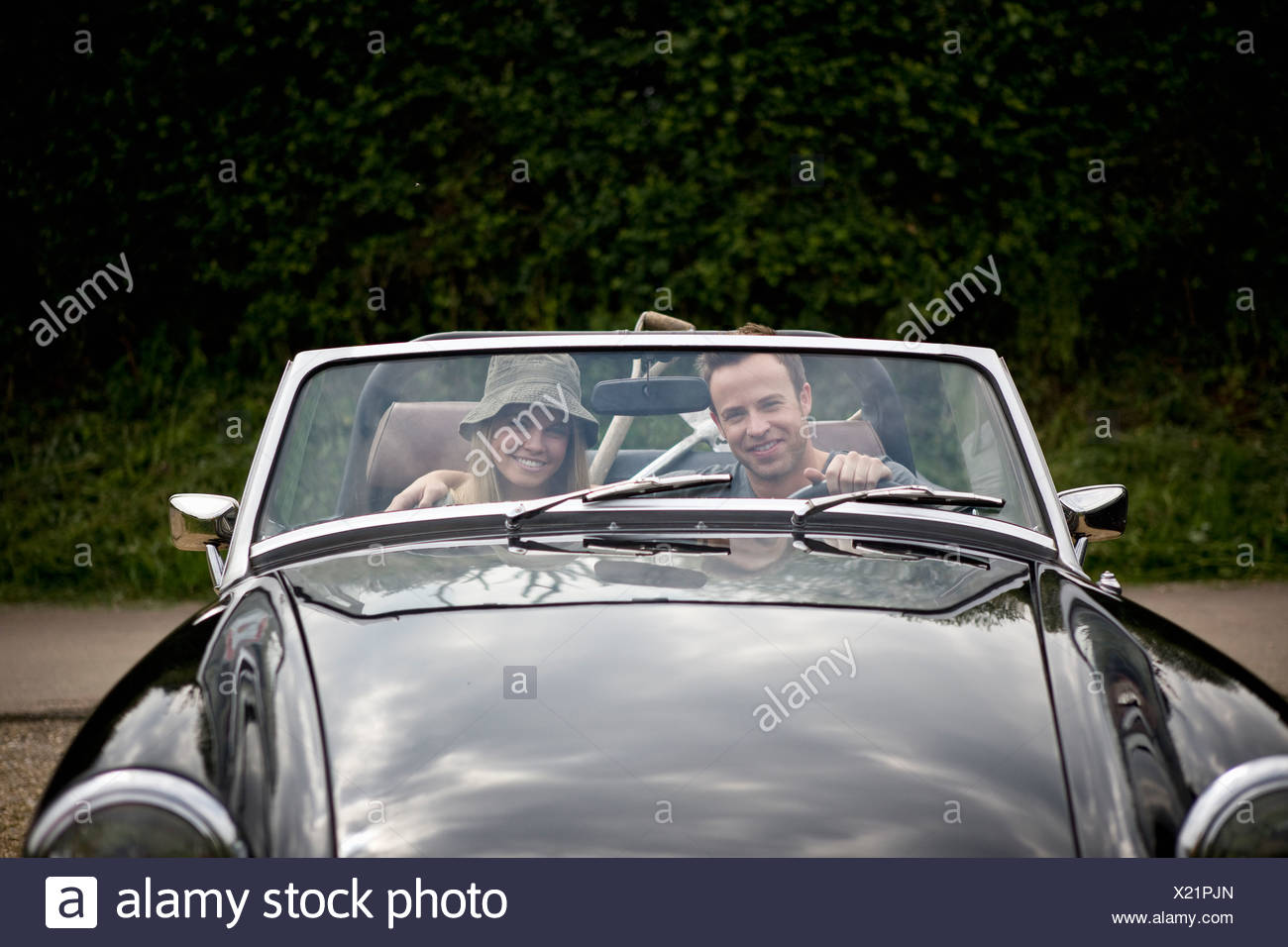 Ein junges Paar fährt einen schwarzen Sportwagen mit Gartengeräten in den Rücken Stockbild