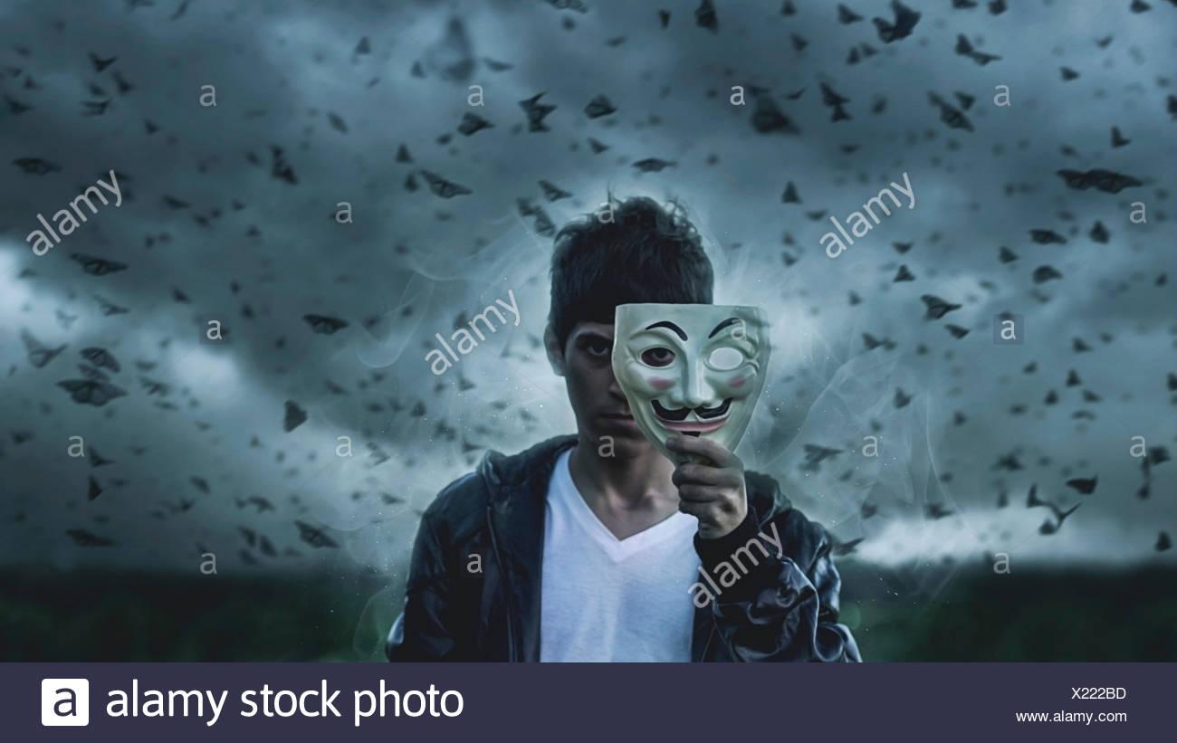 Mann mit Maske vor dem Gesicht mit Schmetterlingen im Hintergrund Stockbild