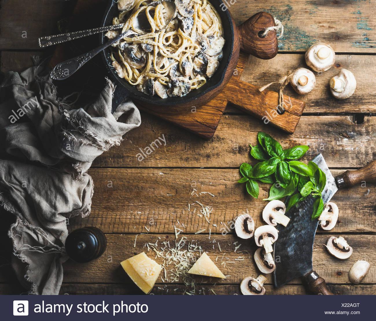 Abendessen im italienischen Stil mit Textfreiraum. Cremige Champignon Nudeln Spaghetti in Gusseisen Pfanne mit Parmesan-Käse, frischem Basilikum und pep Stockbild