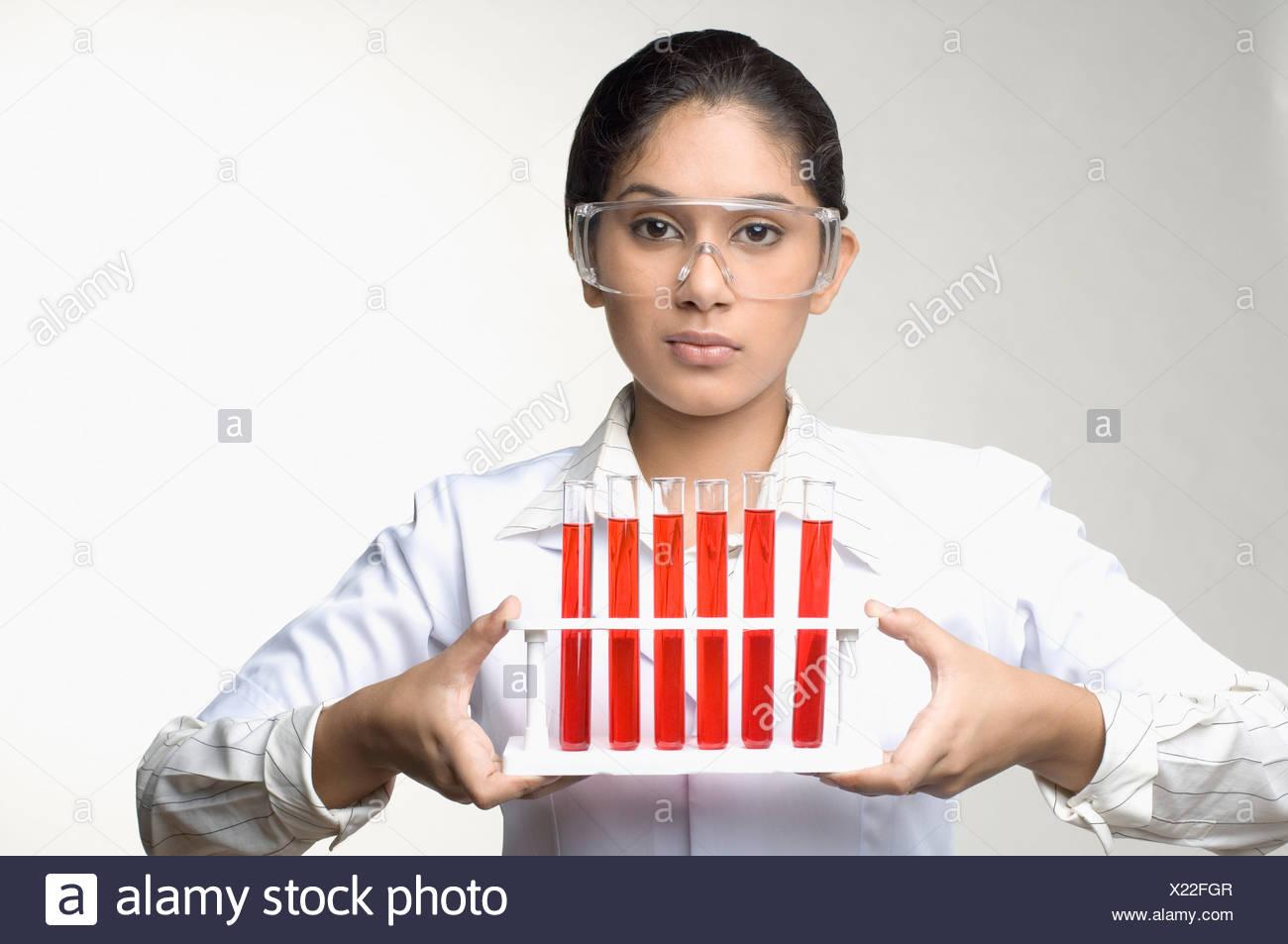 Porträt von einer weiblichen Laborantin hält ein Reagenzglas-Gestell Stockbild