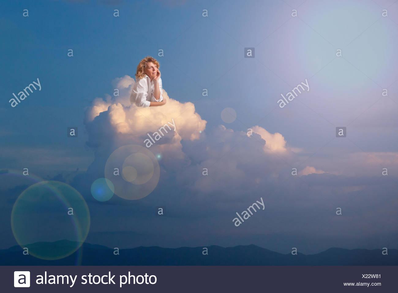 Blonde Frau träumen auf Wolke Stockbild