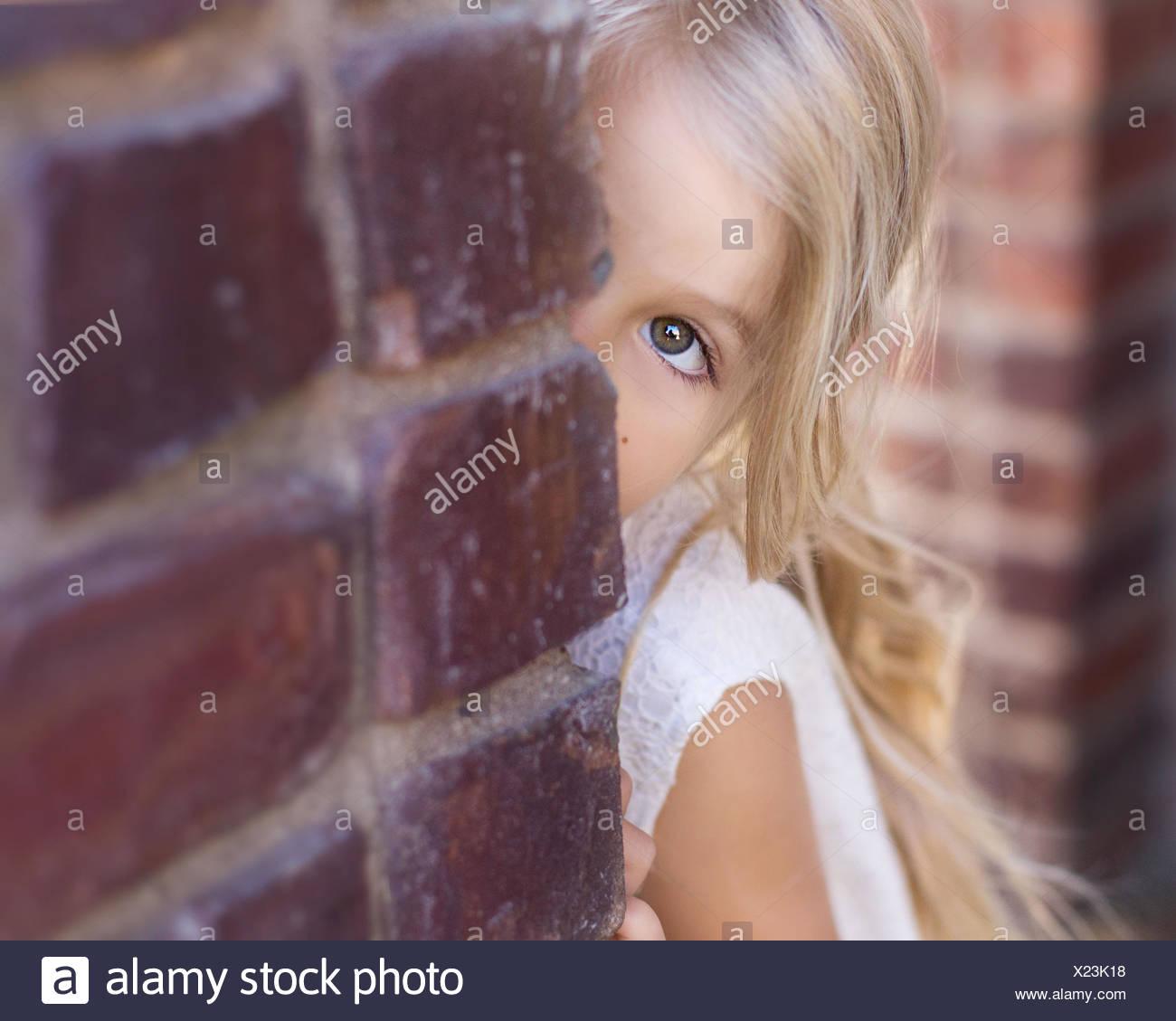 Mädchen, spähen, um eine Mauer Stockbild
