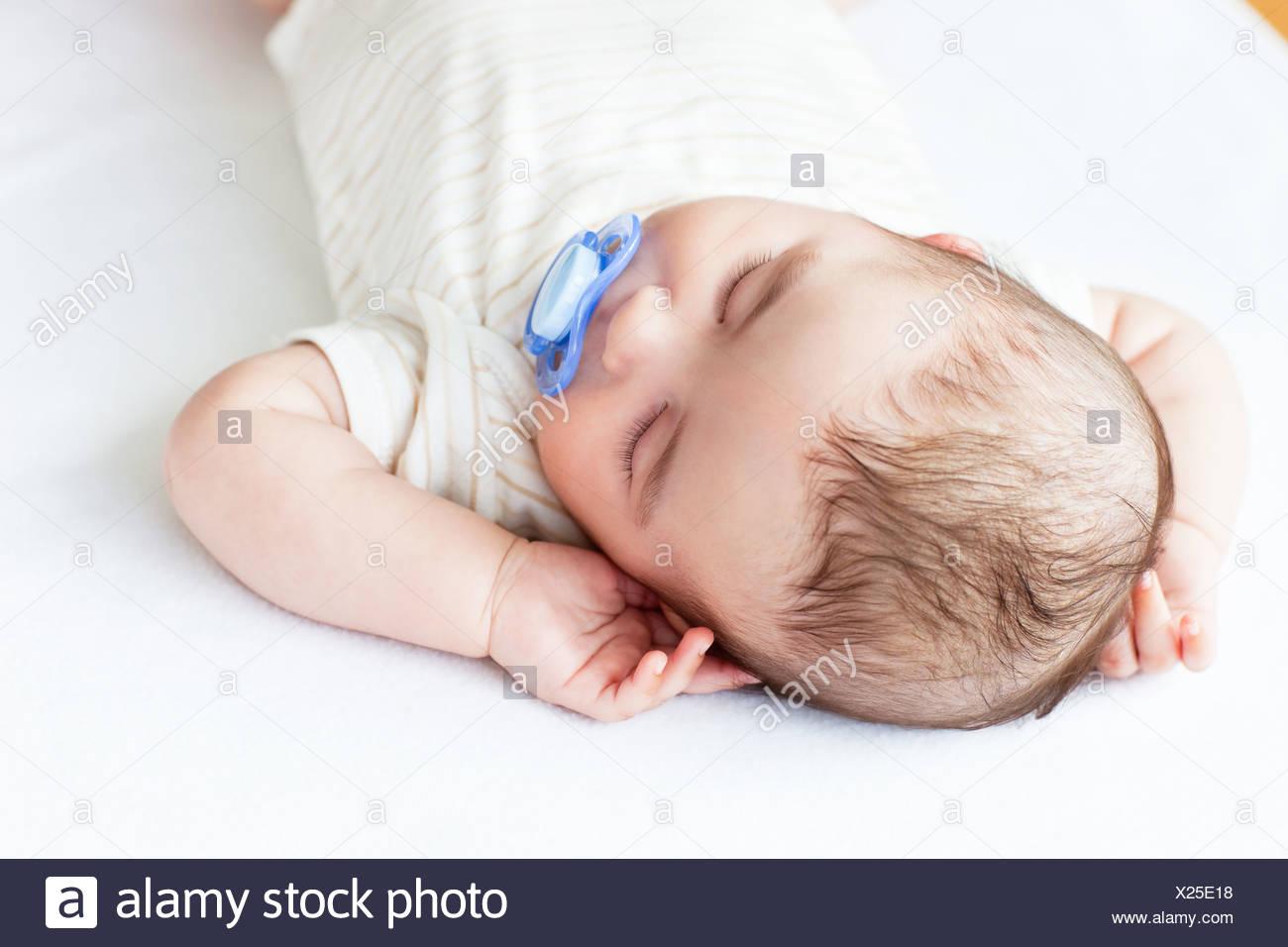 Porträt eines entzückenden Baby mit einem Schnuller schlafen in einem Bett Stockbild