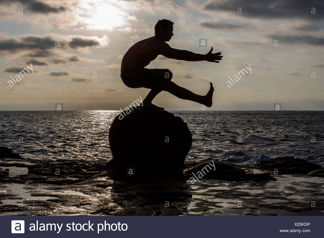 Die Silhouette der ein nackter Oberkörper CrossFit Athlet während er eine Pistole oder einbeinige Kniebeugen auf einem Felsen in den Pazifischen Ozean in San Diego, Kalifornien bei Sonnenuntergang durchführt. Stockbild