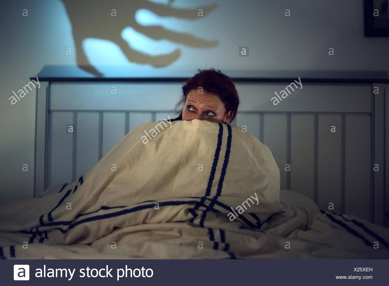 Verängstigte Frau im Bett, gruselige Schatten ein Skelett Hand hinten Stockfoto