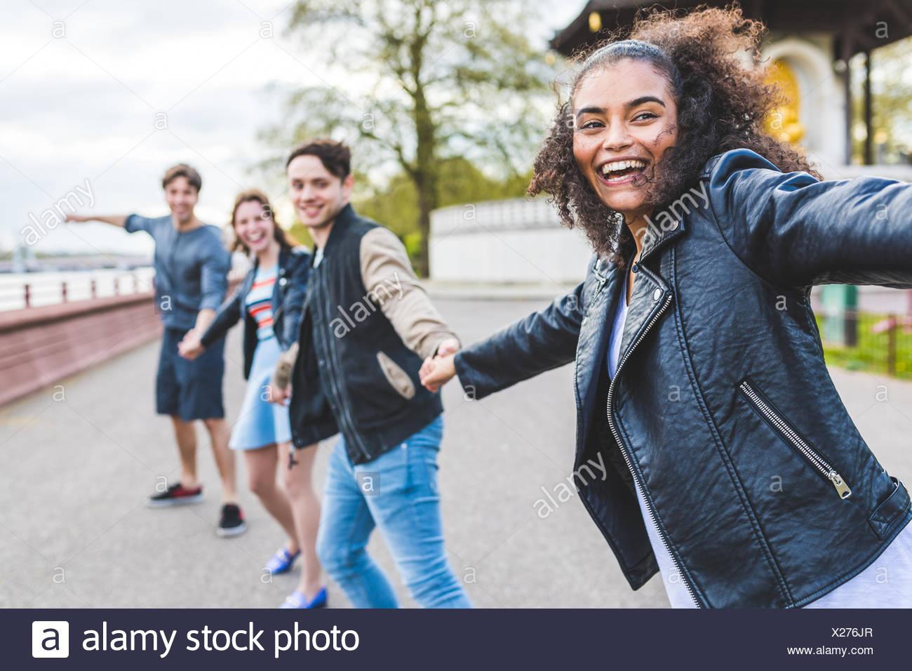 Vier junge erwachsene Freunde halten sich an den Händen in Battersea Park Stockbild