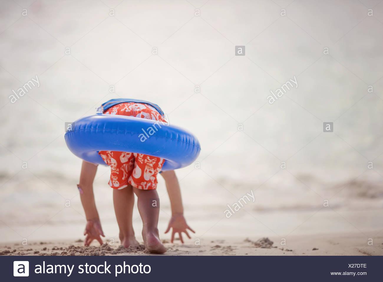 Jungen tragen einen Gummiring am Strand, Playa del Carmen, Mexiko Stockbild