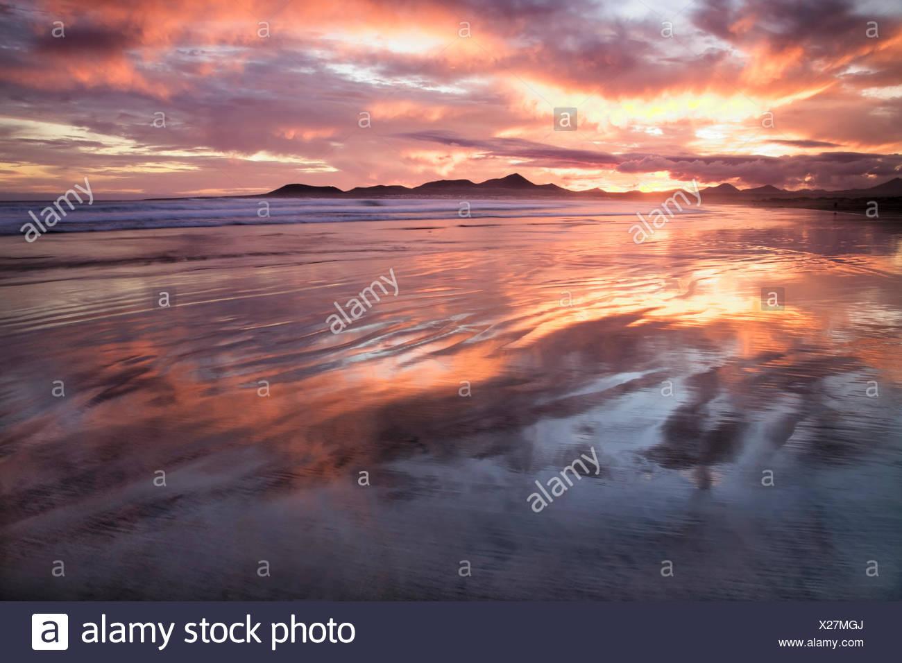 Sonnenuntergang reflektieren über Strand von Famara, Lanzarote, Kanarische Inseln, Spanien, Europa Stockfoto