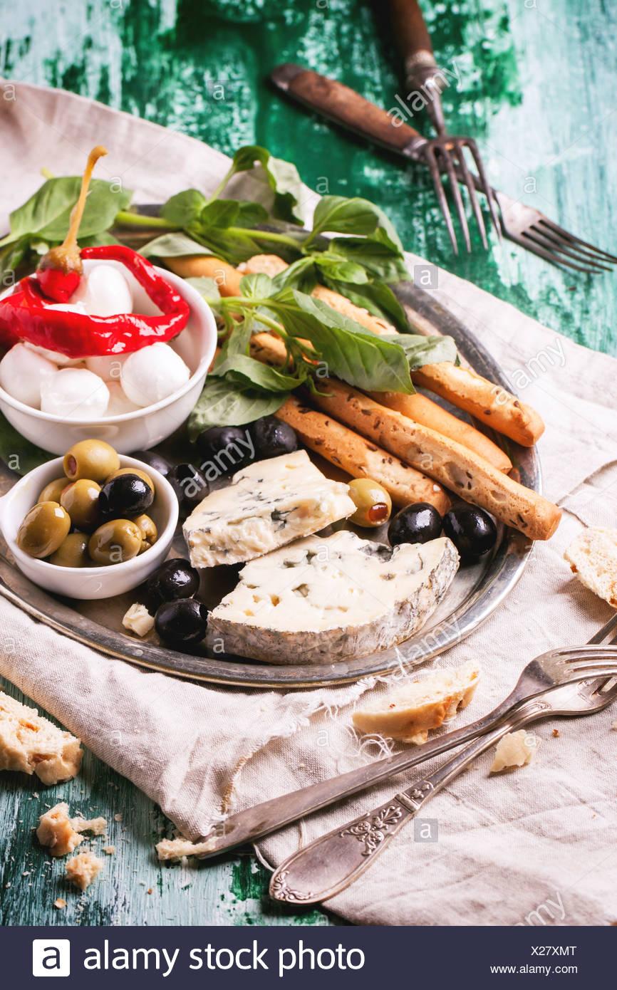 Gemischte Antipasti Blauschimmelkäse, Oliven und Mozarella auf silbernen Tablett über grüne Holztisch mit serviert Vintage Gabeln. Stockbild