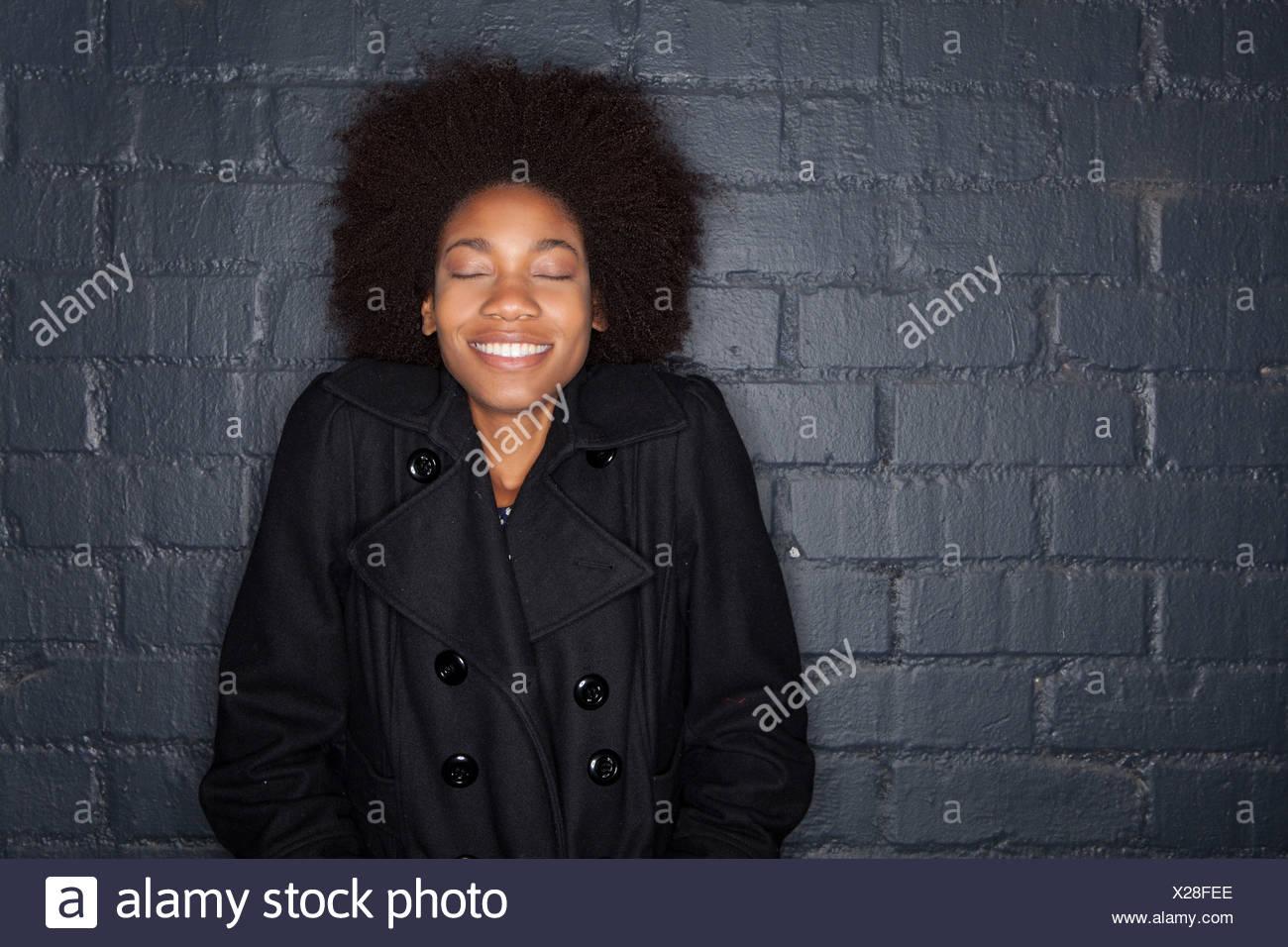 Junge Frau durch das schwarze Ziegel Wand tragen schwarze
