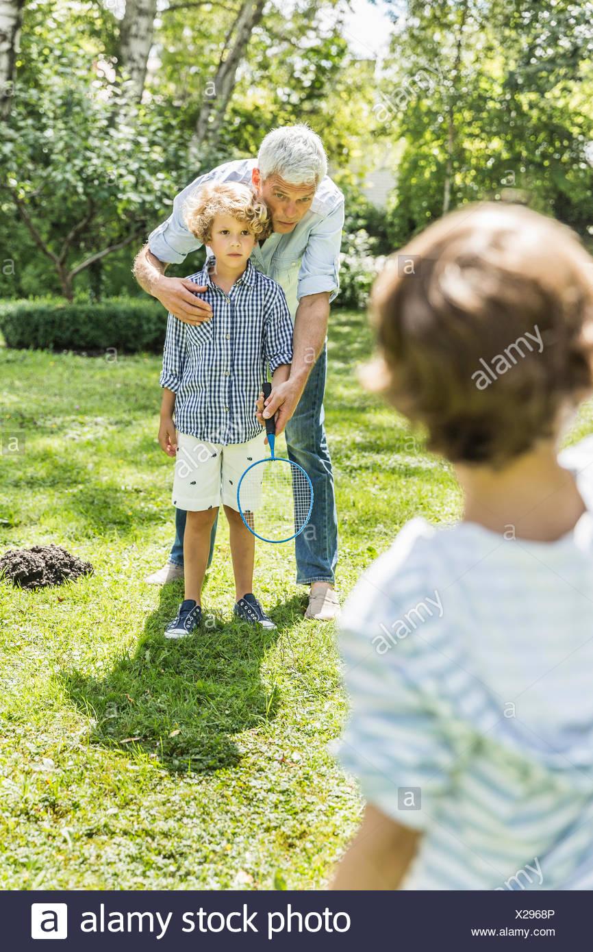 Reifer Mann Lehre Enkel Federball im Garten Stockbild