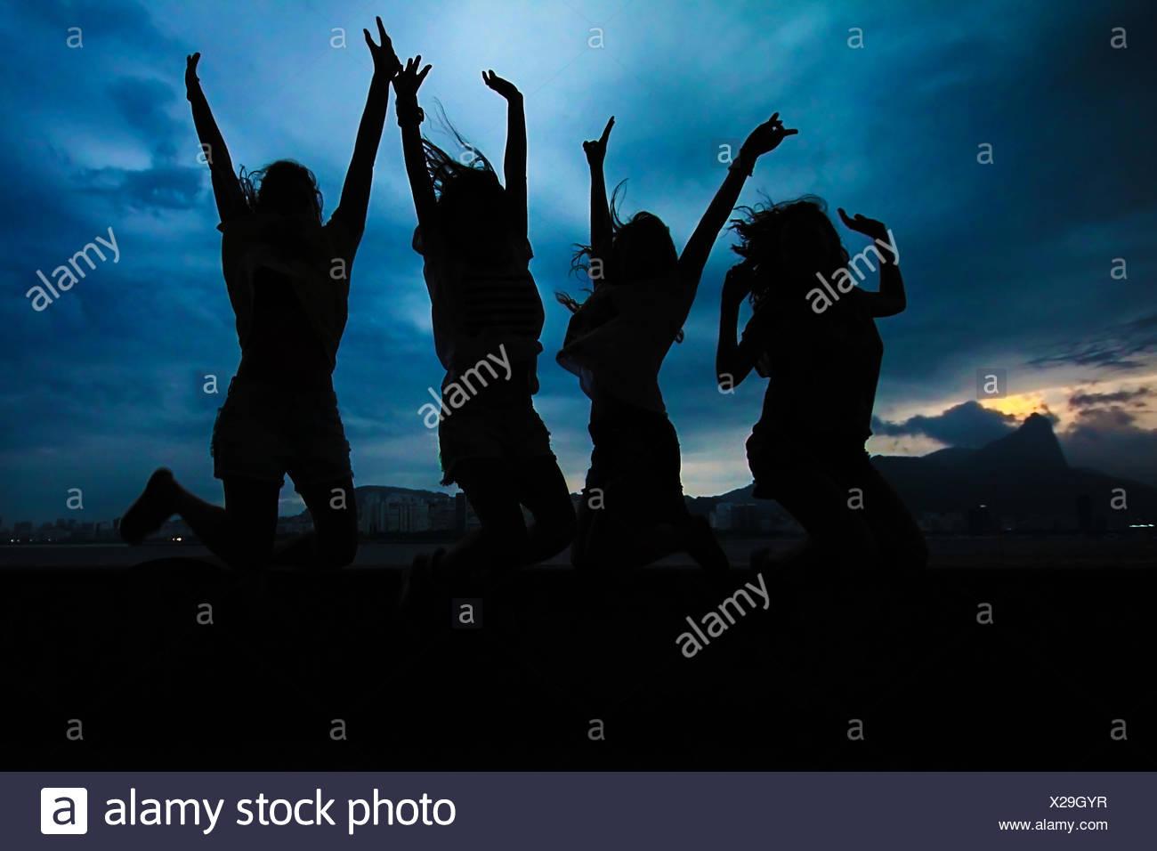 Silhouette von vier Frauen, die in die Luft springen Stockbild