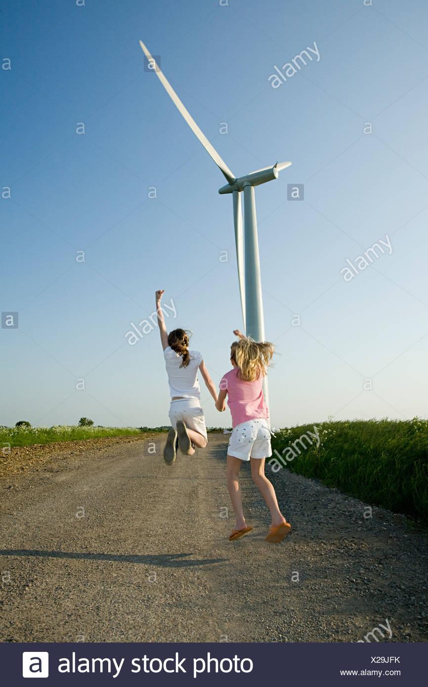 Mädchen springen in der Nähe von Windkraftanlagen Stockbild