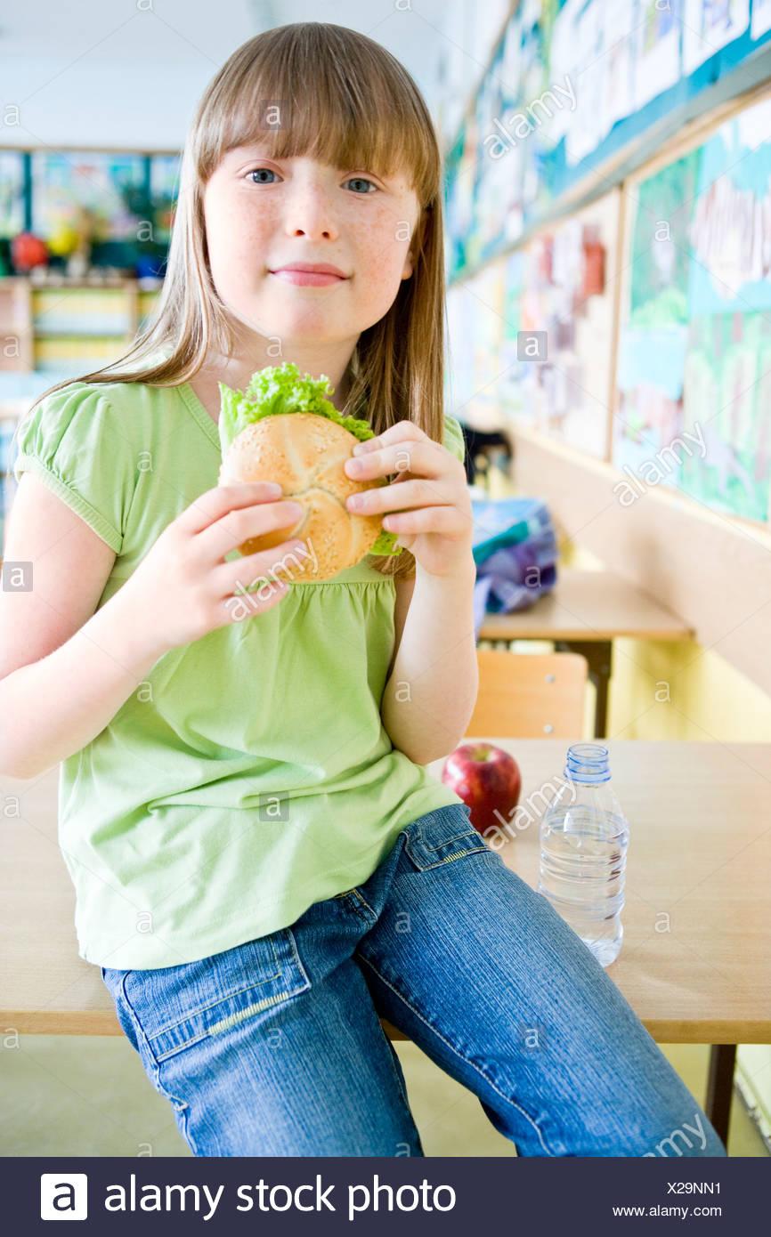 Mädchen beim Mittagessen in der Schule Stockbild