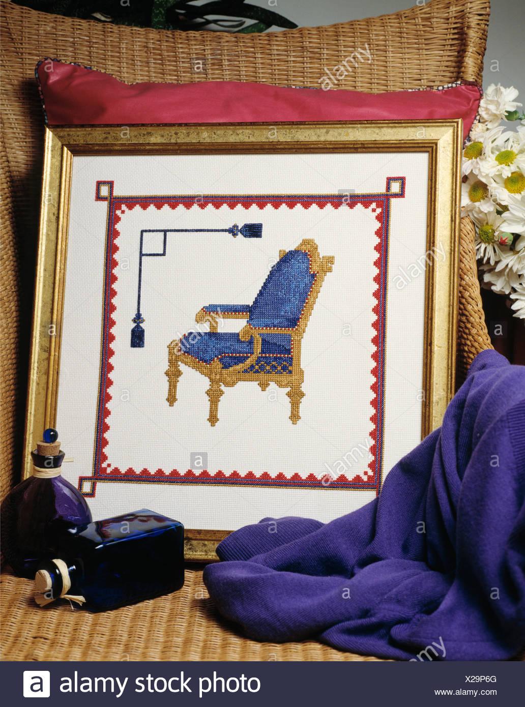 Nahaufnahme von Wicker Sessel mit gerahmten Kreuzstich Bild der ...