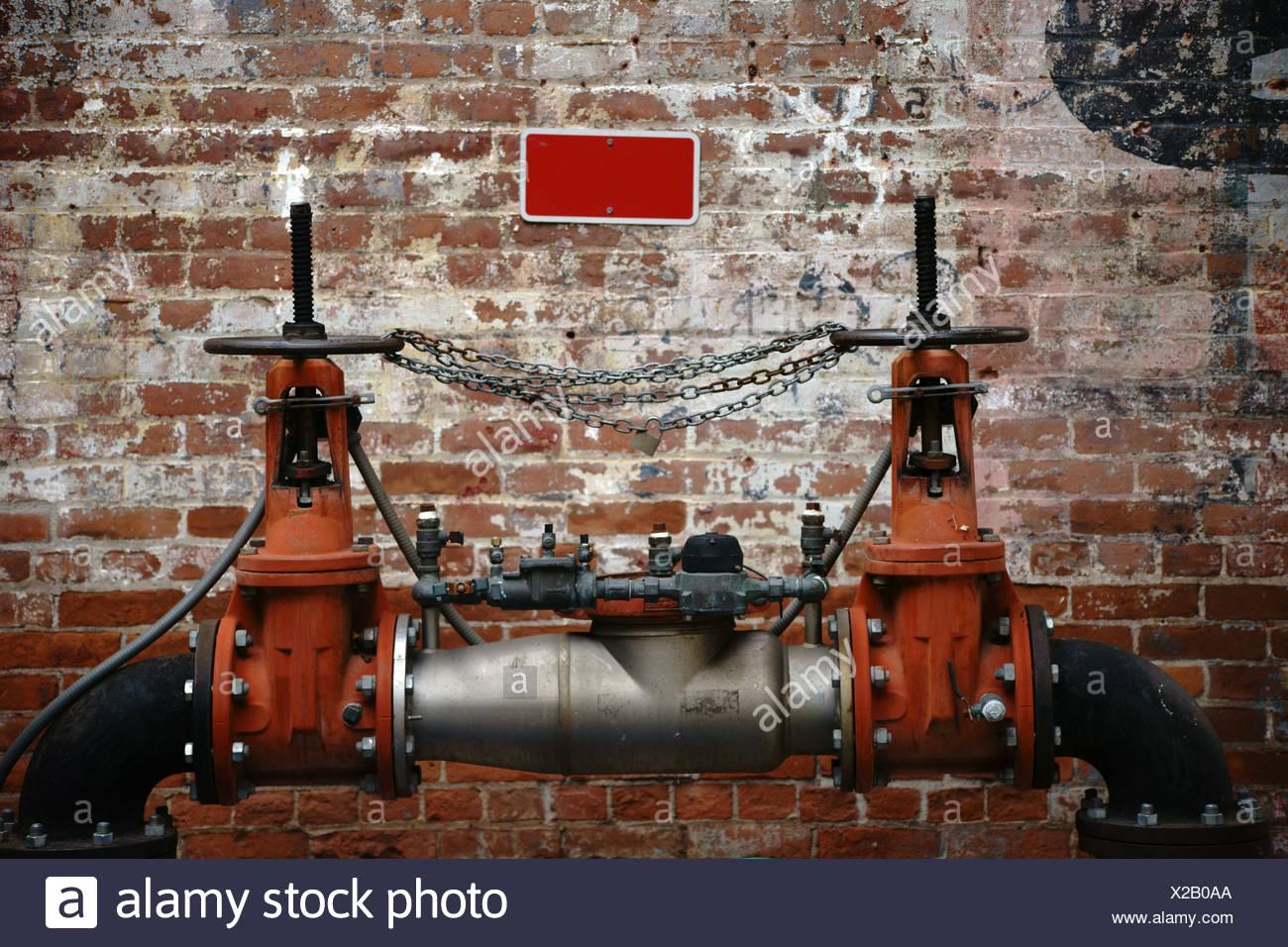 Eine Pumpstation e vor einer alten Backsteinwand mit verblichenen Schriftzeichen und Farbschichten. Stockbild