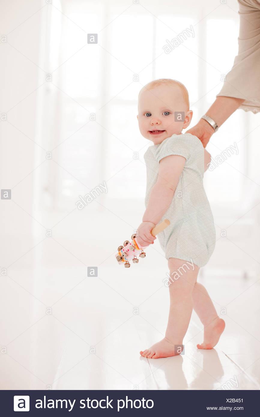Eltern helfen Baby gehen Stockbild