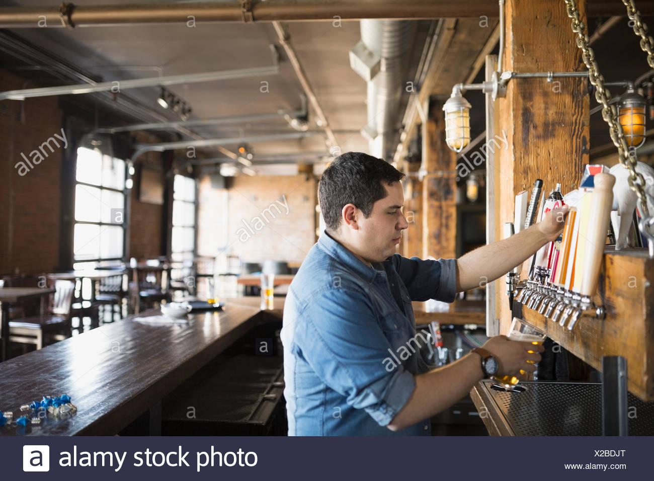 Barkeeper Gießen Bier vom Fass Stockbild