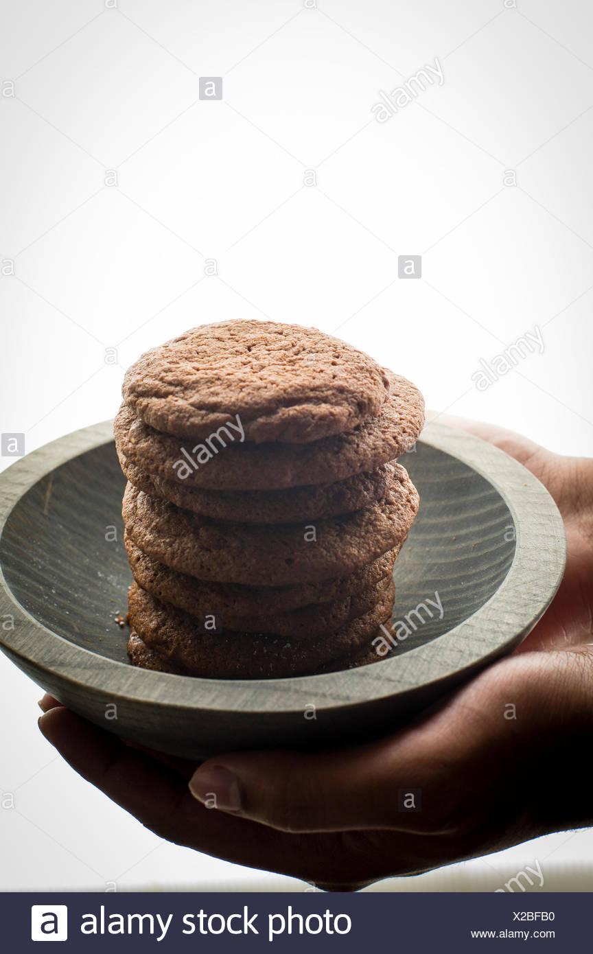 Stapel von Brownie Cookies in einem grauen Holzschale Modell Hände auf Schuss hinterleuchtet Stockbild