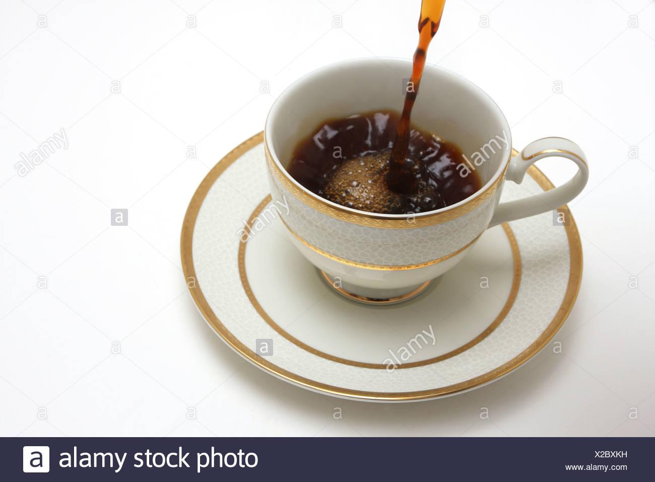 Ein Sideview Schuss für eine Tasse Kaffee isoliert auf weißem, Kaffee hinein gegossen Stockbild