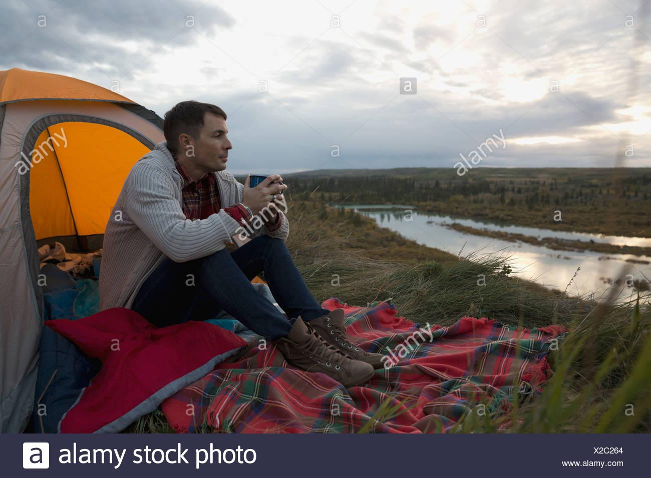 Voller Länge des Mannes Kaffeetrinken auf Campingplatz Stockbild