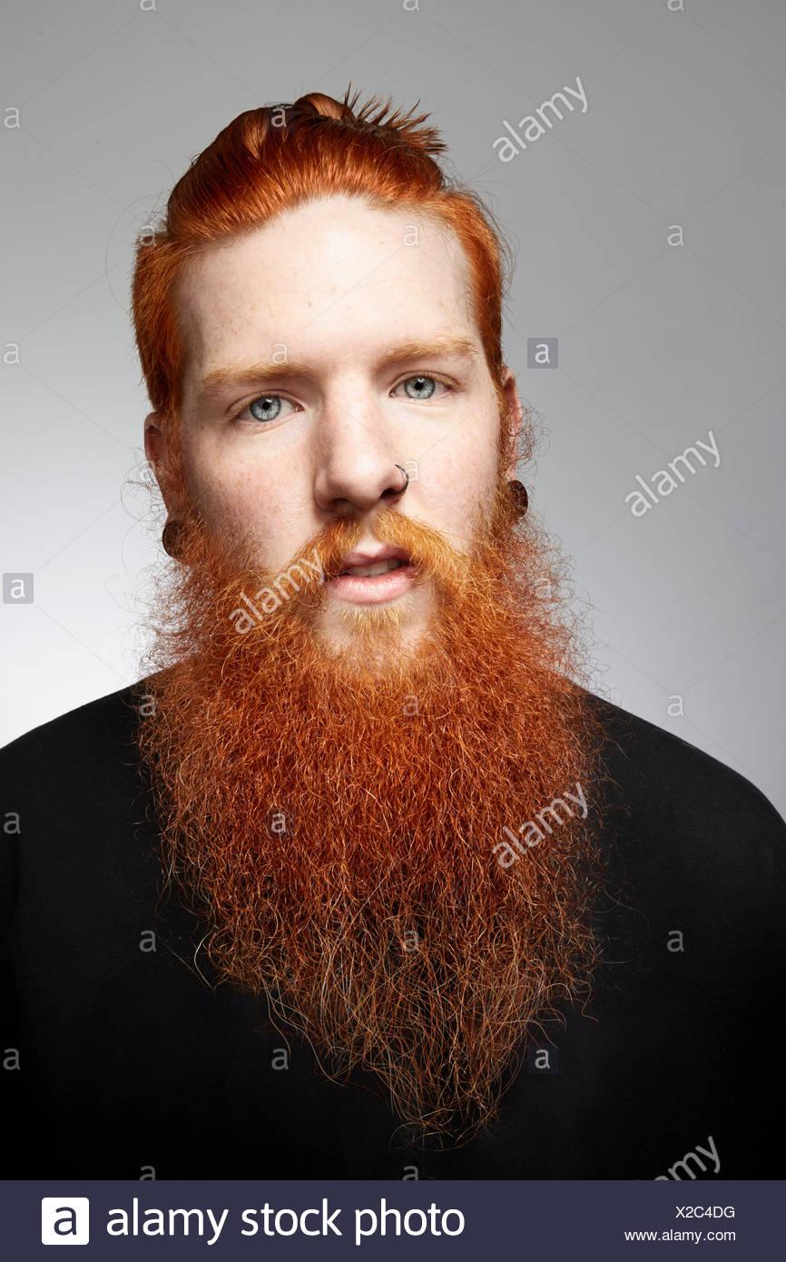 Studioportrait von starren junger Mann mit roten Haaren und verwilderten Bart Stockfoto