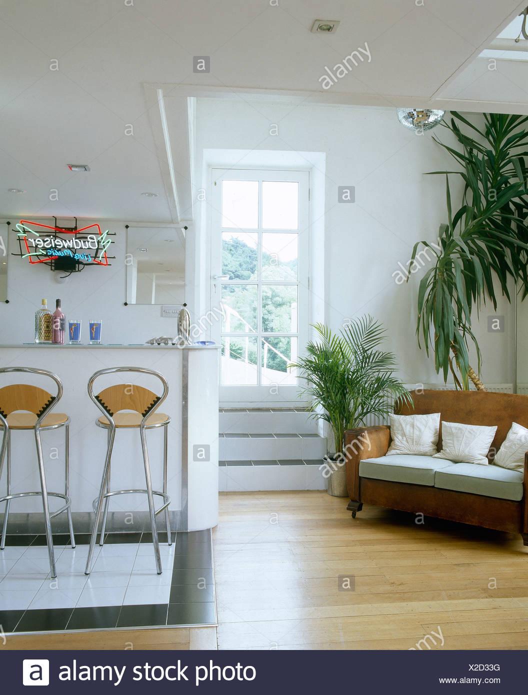 Holzböden und große Zimmerpflanzen neben Sofa im Wohnzimmer ...