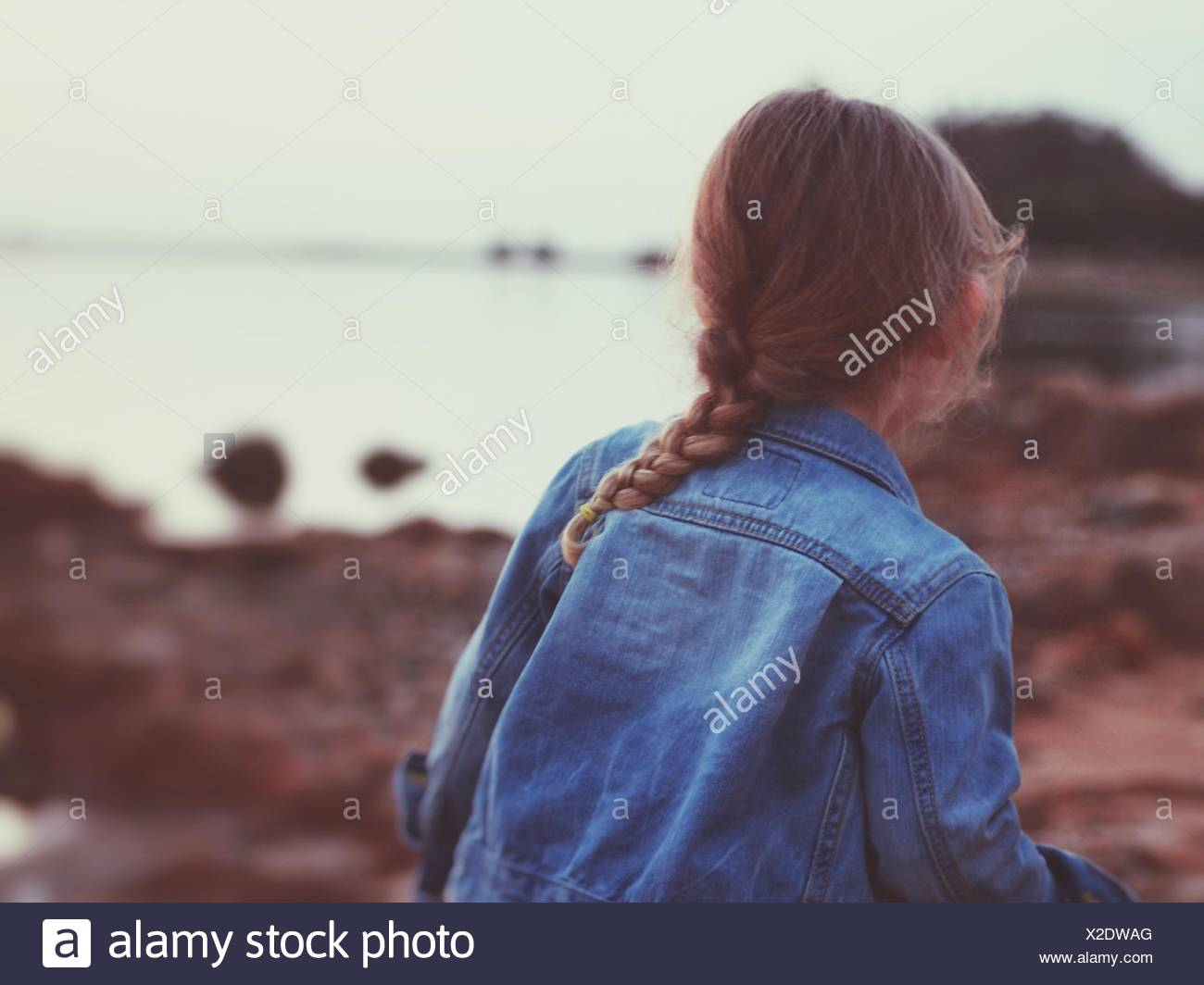 Rückansicht des Mädchens tragen Jeansjacke am Strand Stockbild