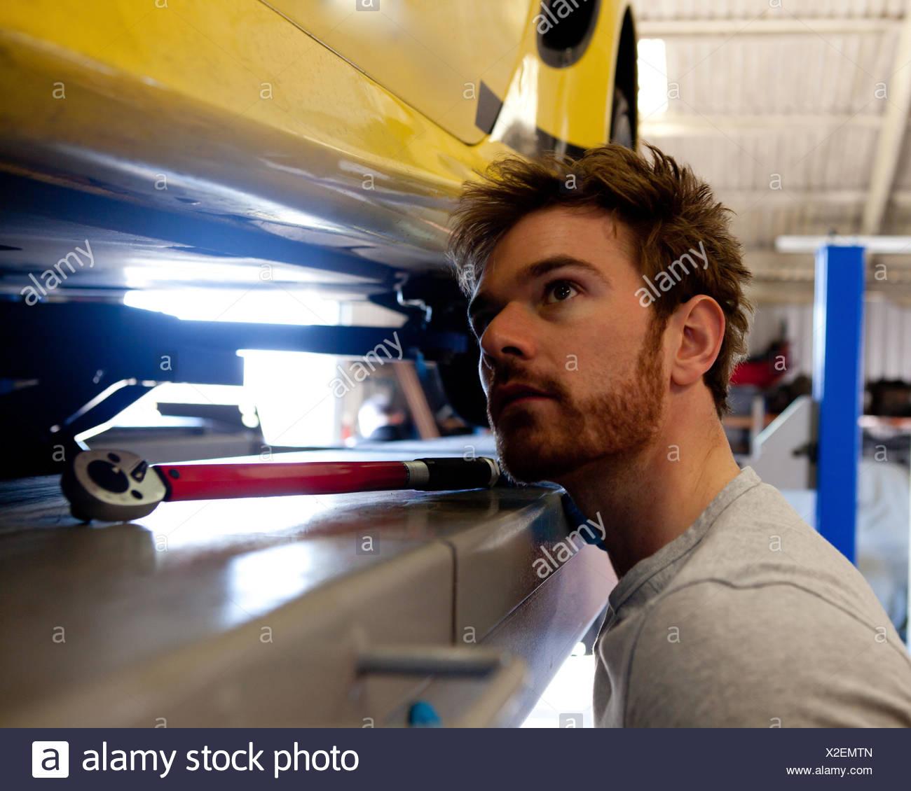 Männliche Mechaniker suchen unter Sportwagen Stockbild