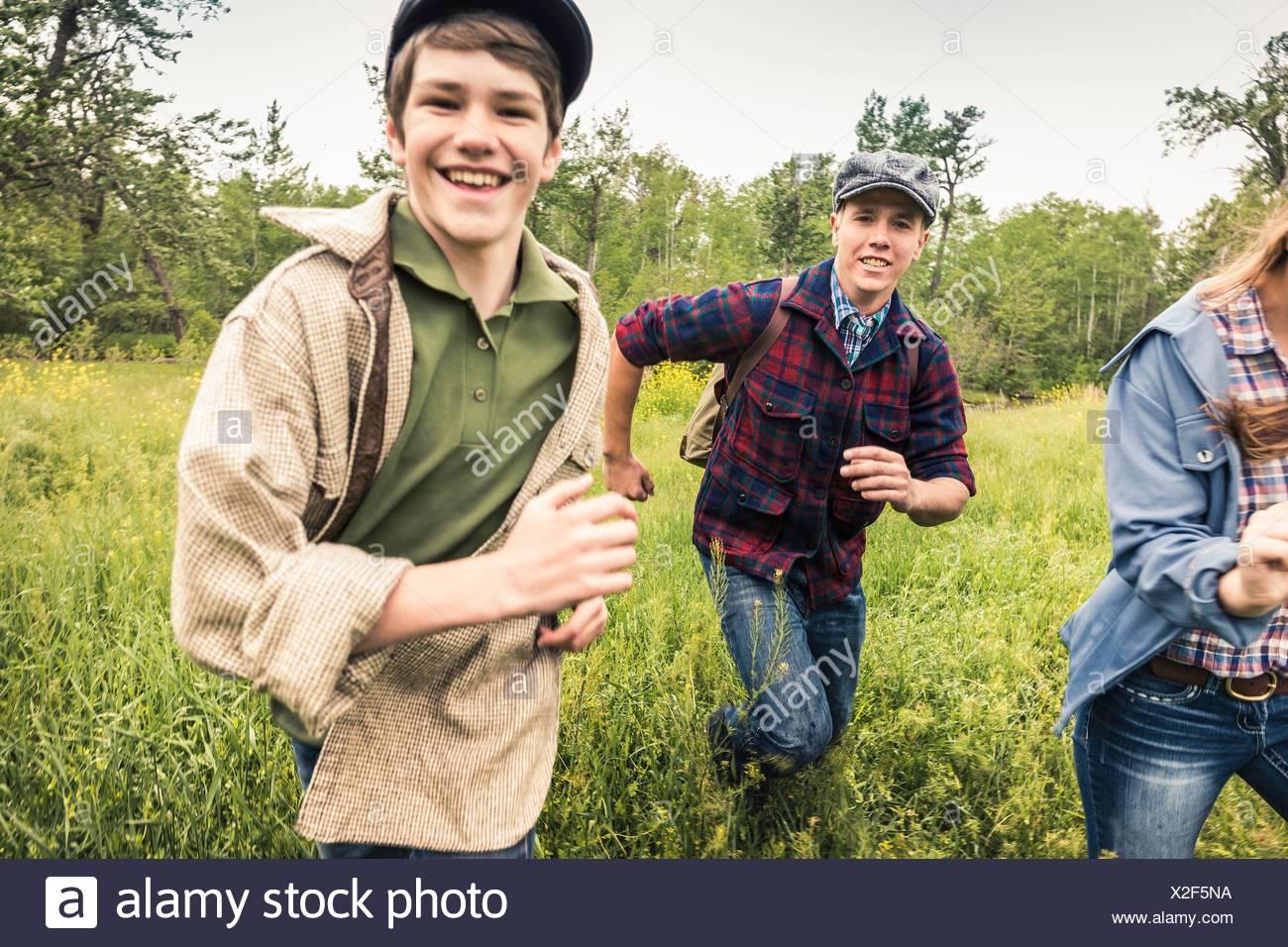 Junge Erwachsene und teenboy trägt Schiebermütze läuft in hohe Gräser, Blick auf die Kamera zu Lächeln Stockbild