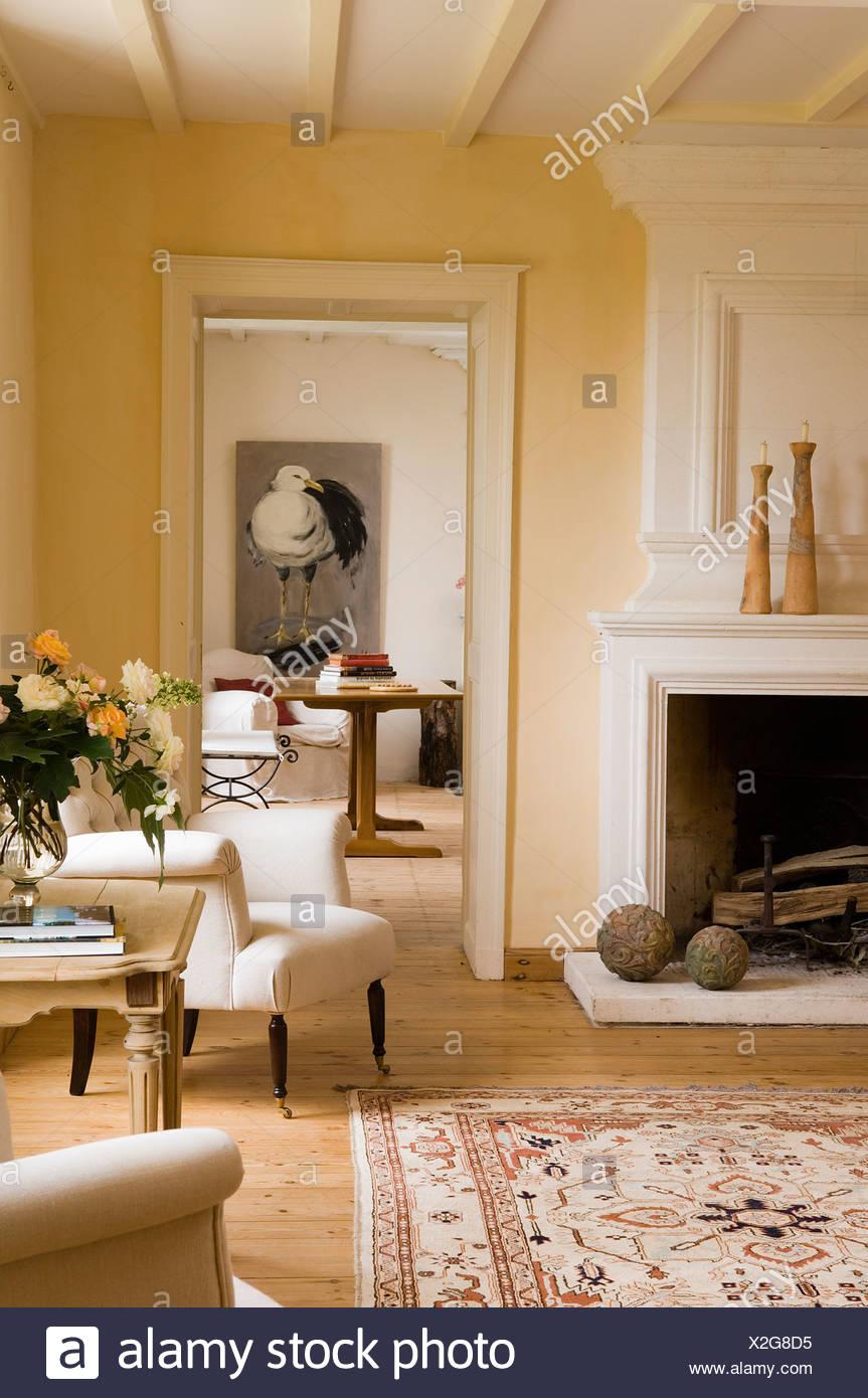 Cremefarbenen Gepolsterten Sessel Am Kamin In Franzosischer Landhaus Wohnzimmer Mit Offener Tur Zum Speisesaal Stockfotografie Alamy